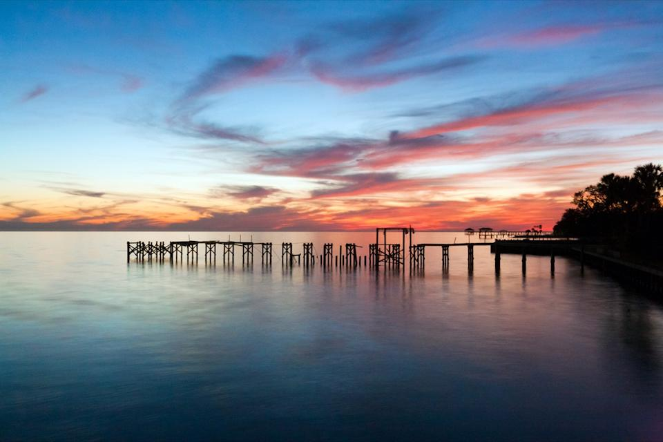 a pier over and trees next to Lake Pontchartrain in Mandeville Louisiana at sunset