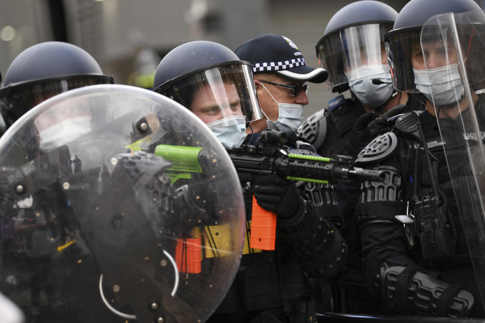 Police are dressed in riot gear during an anti-lockdown protest in Melbourne, Australia, Saturday, Aug. 21, 2021. Protesters are rallying against government restrictions placed in an effort to reduce the COVID-19 outbreak. (James Ross/AAP Image via AP)