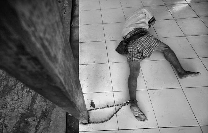 """<b>Honorable Mention: Captive</b> <br> Yayasan Galuh Rehabilitation Center is and impoverished mental health facility based in Bekasi, Indonesia that hosts over 250 patients. Most come from poor families no longer interested in managing their condition, or are unable. Some patients are homeless, deposited after being taken off streets by police. The only medical treatment received is for skin conditions. No assessments, psychotherapy or psychiatric medications is available. Over one third of the patients are shackled in chains. These measures are implemented to those thought to be violent, uncontrollable and dangerous. <a href=""""http://ngm.nationalgeographic.com/ngm/photo-contest/"""" rel=""""nofollow noopener"""" target=""""_blank"""" data-ylk=""""slk:(Photo and caption by Wendell Phillips/National Geographic Photo Contest)"""" class=""""link rapid-noclick-resp"""">(Photo and caption by Wendell Phillips/National Geographic Photo Contest)</a>"""