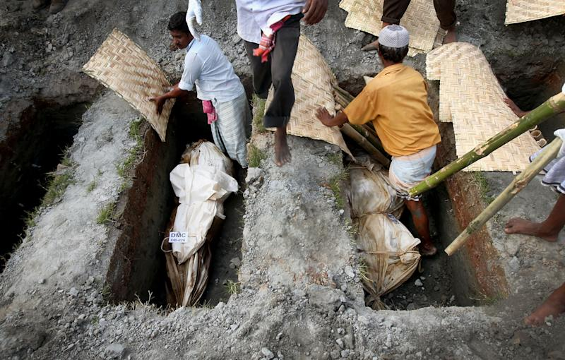 Workers bury unclaimed bodies from the garment factory building collapse in preparation for a mass burial on Wednesday May 1, 2013 in Dhaka, Bangladesh. Several hundred people attended a mass funeral in a Dhaka suburb for 18 unidentified workers who died in the building collapse last week in the country's worst industrial disaster, killing at least 402 people and injuring 2,500. The bodies, rotting in the spring heat, were brought to the graveyard on the back of a flatbed truck. (AP Photo/Wong Maye-E)