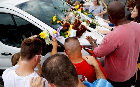 People pray around a van believed to belong to victims of a duck boat accident - Credit: Charlie Riedel/AP