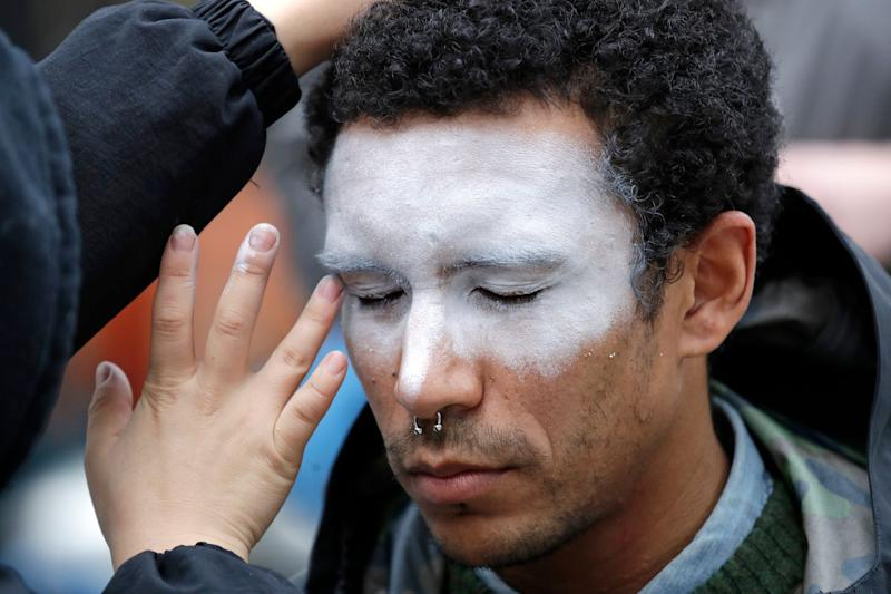 """In this Oct. 31, 2018, file photo, a man, who declined to be identified, has his face painted to represent efforts to defeat facial recognition during a protest at Amazon headquarters over the company's facial recognition system, """"Rekognition,"""" in Seattle. San Francisco is on track to become the first U.S. city to ban the use of facial recognition by police and other city agencies."""