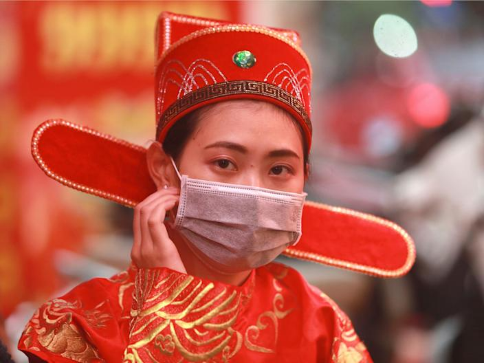 A woman in costume of the Prosperity and Wealth God wears a protective face mask at a gold shop in Hanoi, Vietnam, on February 3, 2020..