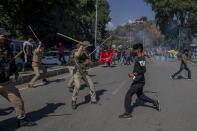 A Kashmiri Shiite Muslim tries to hit a policeman with knives attached to iron chains, used for self flagellation, after being stopped during a religious procession in central Srinagar, Indian controlled Kashmir, Tuesday, Aug. 17, 2021.Police in Indian-controlled Kashmir on Tuesday fired tear gas and warning shots to disperse hundreds of Shiite Muslims, while detaining dozens who attempted to participate in processions marking the Muslim month of Muharram. (AP Photo/Dar Yasin)