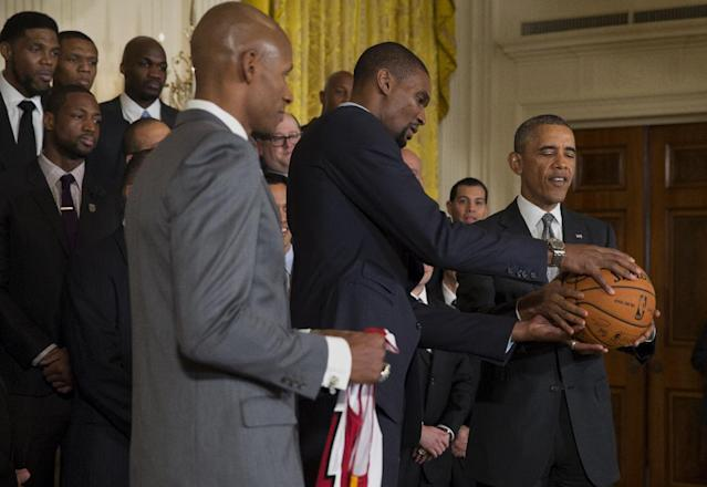 Miami Heat player Ray Allen, left, holds a Miami Heat jersey as fellow player Chris Bosh presents President Barack Obama with a signed basketball after the president honored the 2013 NBA Champion basketball team during a ceremony in the East Room of the White House, Tuesday, Jan. 14, 2014, in Washington. (AP Photo/Jacquelyn Martin)
