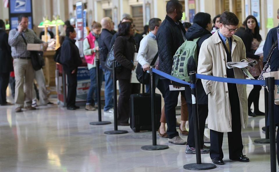 People wait in line inside the James A. Farley post office building April 15, 2013 in the Manhattan borough of New York City. For Canadians, the filing deadline is May 1, and you probably want to avoid being in a situation like this. (Getty)