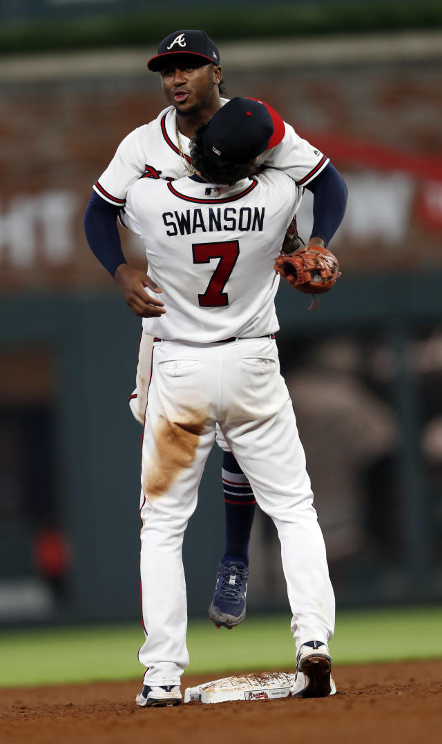 Atlanta Braves shortstop Dansby Swanson (7) and second baseman Ozzie Albies celebrate after they defeated the Milwaukee Brewers in a baseball game Friday, Aug. 10, 2018, in Atlanta. (AP Photo/John Bazemore)