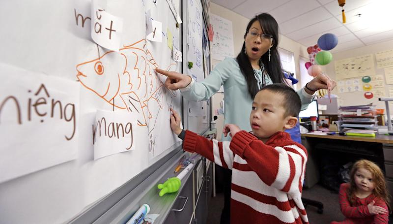 In this photo taken Friday, Feb. 14, 2014, kindergarten teacher Thao Tran helps student Brian Ho learn fish anatomy in Vietnamese in a dual immersion language class at White Center Heights Elementary School in Seattle. In a handful of schools across the country, kindergartners aren't being taught just in English, but also in Vietnamese. The move to add Vietnamese to the growing list of languages featured in dual immersion education classes comes as the American born children of Vietnamese immigrants are striving to preserve their family's heritage for the next generation. (AP Photo/Elaine Thompson)