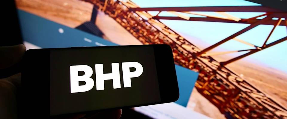 Person holding smartphone with logo of mining, metals and petroleum company BHP Group on screen in front of website.