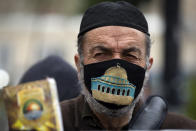 A Palestinian man wearing a face mask embroidered with an image of the Al-Aqsa Mosque takes part in a demonstration demanding protection from the coronavirus for Palestinians in Israeli jails, in the West Bank city of Ramallah, Sunday, Jan. 31, 2021. (AP Photo/Majdi Mohammed)