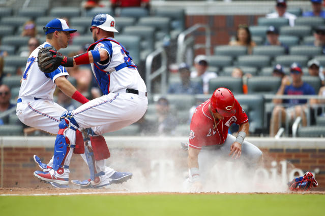 Cincinnati Reds Derek Dietrich (22) slides into home to score off a sacrifice bunt of Sonny Gray in the fourth inning of a baseball game against the Atlanta Braves, Sunday, Aug.4, 2019, in Atlanta. (AP Photo/Todd Kirkland)