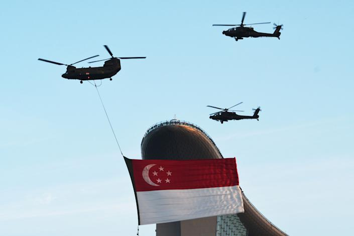 A helicopter towing the Singapore national flag flies in formation during the National Day Parade rehearsal held at Singapore's Marina Bay on 17 July. (PHOTO: Getty Images)