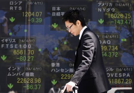 A man walks past at an electronic board displaying various countries' share prices outside a brokerage in Tokyo