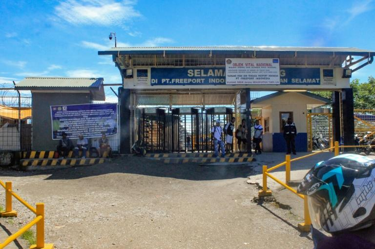 Employees from the Freeport-McMoRan mine stand at the entrance of a bus terminal in Timika, Papua