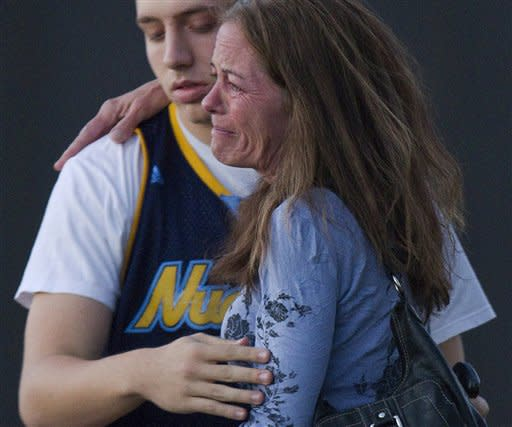 """Jacob Stevens, 18, hugs his mother Tammi Stevens after being interview by police outside Gateway High School where witness were brought for questioning after a shooting at a movie theater, Friday, July 20, 2012 in Denver. A gunman wearing a gas mask set off an unknown gas and fired into a crowded movie theater at a midnight opening of the Batman movie """"The Dark Knight Rises,"""" killing at least 12 people and injuring at least 50 others, authorities said. (AP Photo/Barry Gutierrez)"""