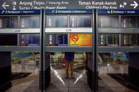 A man stand near flight information boards at Kuala Lumpur International Airport (KLIA) outside Kuala Lumpur June 14, 2014. REUTERS/Samsul Said/File Photo