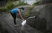 FILE - In this April 22, 2020, file photo, a woman wearing a face mask as a precaution from the coronavirus collects water on the side of the road to take home in Caracas, Venezuela. For people around the world who are affected by war and poverty, the simple act of washing hands is a luxury. (AP Photo/Ariana Cubillos)