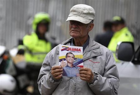 A supporter holds a leaflet while waiting for Colombian presidential candidate Oscar Ivan Zuluaga's campaign rally in the Bogota neighborhood of Suba