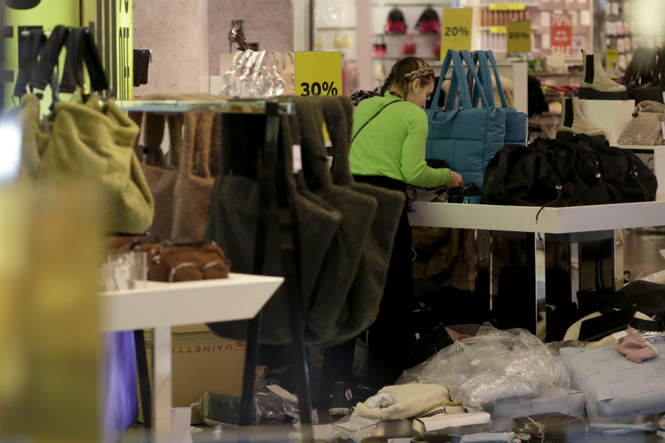 A worker is seen through the front window inside the temporarily closed Topshop flagship store on Oxford Street, during England's second coronavirus lockdown, in London, Monday, Nov. 30, 2020. Arcadia Group, the retail empire of tycoon Philip Green, which owns well-known British fashion chains like Topshop and employs around 15,000 people, appears to be on the brink of collapse following the economic shock of the coronavirus pandemic. (AP Photo/Matt Dunham)