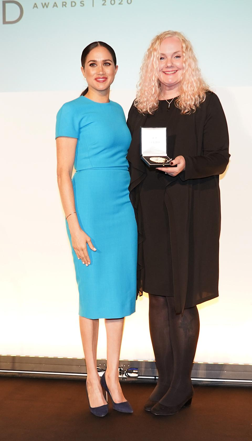 Claire Spencer, 52, (right) accepts the the Celebrating Excellence award on behalf of her husband and former Royal Marine Lee Spencer from the Duchess of Sussex (left) at the Endeavour Fund Awards at Mansion House in London.