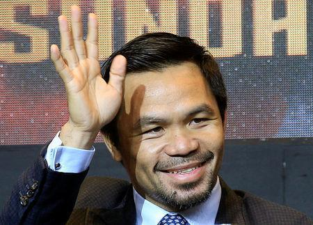 "Philippine senator and boxing icon Manny ""Pacman"" Pacquiao waves during a news conference with welterweight world title holder Lucas Matthysse (not pictured), for their upcoming WBA ""regular"" welterweight title fight in Kuala Lumpur, Malaysia, in a hotel in Paranaque city, metro Manila, Philippines April 18, 2018. REUTERS/Romeo Ranoco"