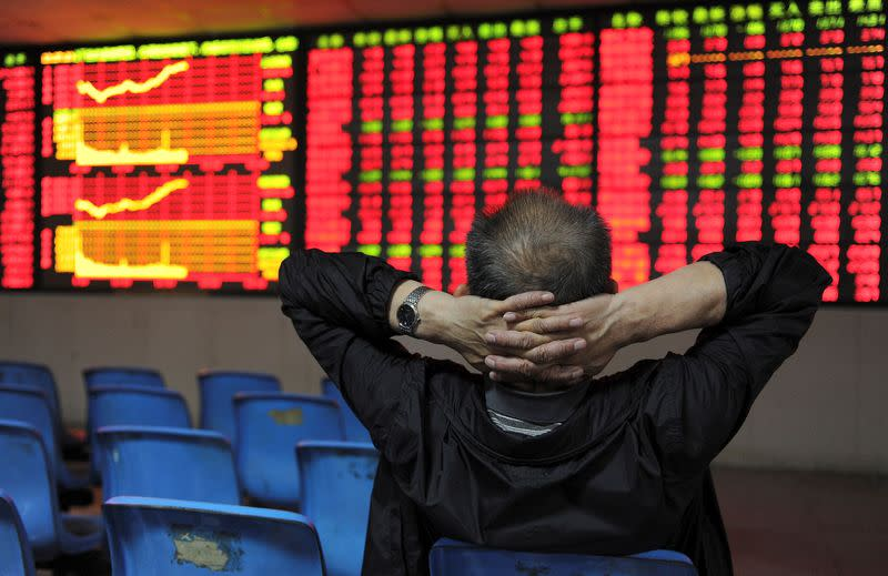FILE PHOTO: An investor places his hands on the back of his head in front of an electronic board showing stock information at a brokerage house in Hefei