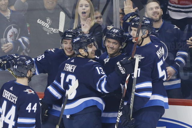 Winnipeg Jets centrer Marko Dano (56), left wing Brandon Tanev (13), center Jack Roslovic (52) and defenseman Tyler Myers (57) celebrate Roslovic's goal against the Chicago Blackhawks during the first period of an NHL hockey game Thursday, March 15, 2018, in Winnipeg, Manitoba. (John Woods/The Canadian Press via AP)