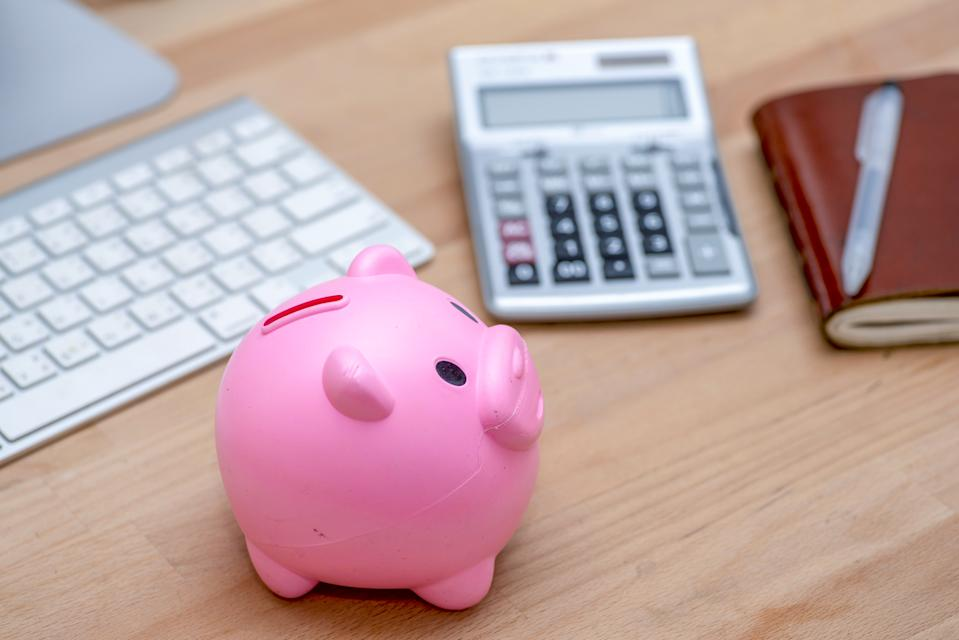 Savings and investment concept, pink piggy bank with calculator on pile or economic analysis report chart and graph on office table.