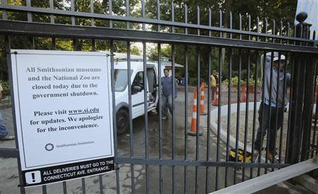 A construction crew works on a project behind the gates of the Smithsonian National Zoo, which is closed due to the government shutdown, in Washington October 2, 2013. REUTERS/Gary Cameron