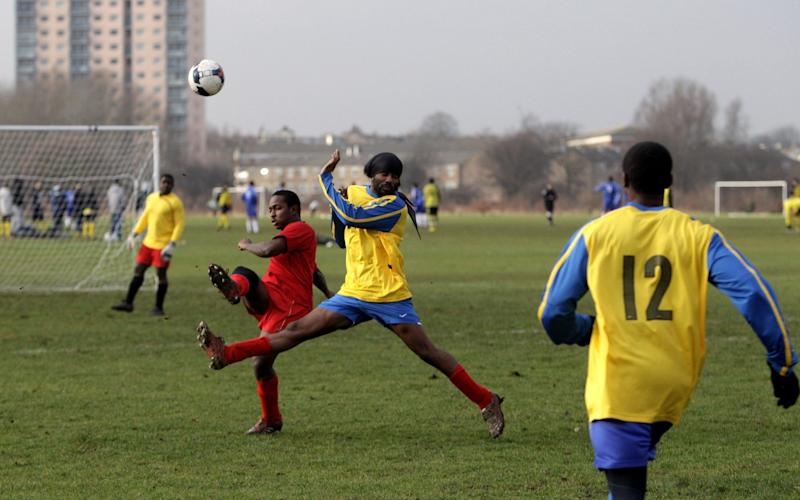 Two Sunday League footballers challenge for the ball during a match on the Hackney Marshes' pitches - GETTY IMAGES