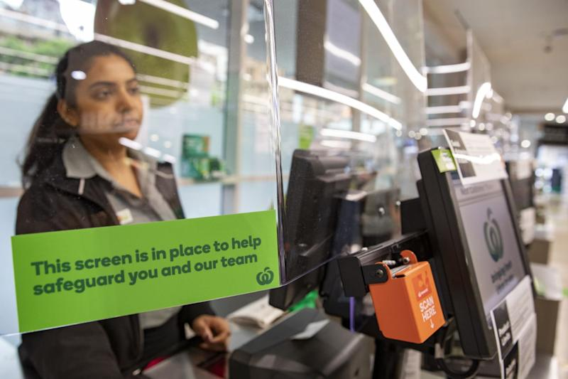 A Woolworths worker is seen looking out from behind a screen installed to protect workers amid the coronavirus pandemic.