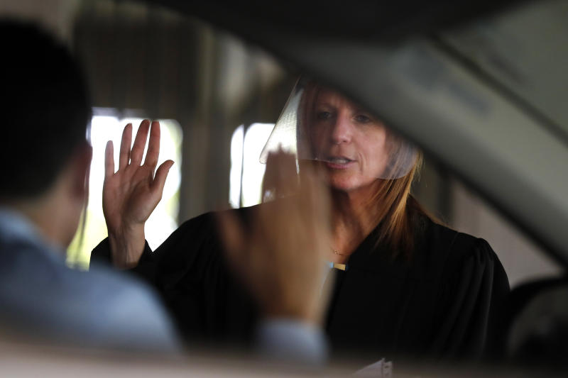 In this June 26, 2020 photo, U.S. District Judge Laurie Michelson administers the Oath of Citizenship to Ismael Gonzalez during a drive-thru naturalization service in a parking structure at the U.S. Citizenship and Immigration Services headquarters on Detroit's east side. The ceremony is a way to continue working as the federal courthouse is shut down due to Coronavirus. The U.S. has resumed swearing in new citizens but the oath ceremonies aren't the same because of COVID-19 and a budget crisis at the citizenship agency threatens to stall them again.  (AP Photo/Carlos Osorio)