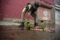An Indian policeman cleans blood splattered on a street with a tree twig after suspected rebels attack on policemen on the outskirts of Srinagar, Indian controlled Kashmir, Friday, Aug. 14, 2020. Anti-India rebels in Indian-controlled Kashmir Friday attacked a police party in the disputed region's main city, killing two police officials and injuring another, police said. (AP Photo/Mukhtar Khan)