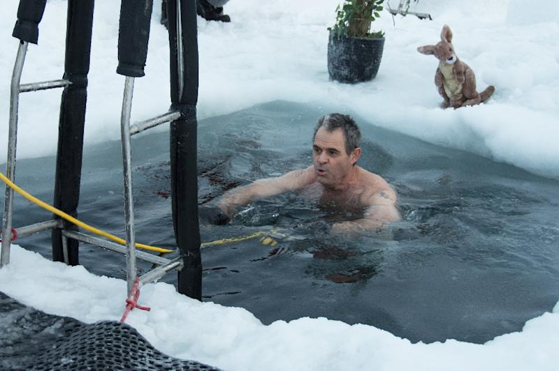 This handout photo taken on June 19, 2018 and released by the Australian Antarctic Division (AAD) on June 21 shows Barry Balkin taking a dip in a swimming hole prepared at the Casey research station as researchers welcome the winter solstice (AFP Photo/George BRETTINGHAM-MOORE)