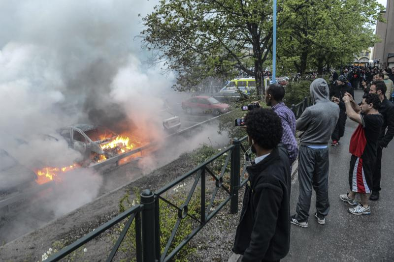 Bystanders take photos of a row of burning cars in the Stockholm suburb of Rinkeby after youths rioted in several different suburbs around Stockholm for a fourth consecutive night, late Thursday May 23, 2013. Youths in immigrant-heavy Stockholm suburbs torched cars and threw rocks at police in riots believed to be linked to a deadly police shooting of a local resident in the suburb of Husby. (AP Photo/Scanpix, Fredrik Sandberg) SWEDEN OUT