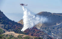 With hand crews on the ground at bottom left, a helicopter drops water onto hot spots from the Silverado Fire off Santiago Canyon Road in Whiting Ranch Wilderness Park on Wednesday, Oct. 28, 2020, near Lake Forest, Calif. (Mark Rightmire/The Orange County Register via AP)