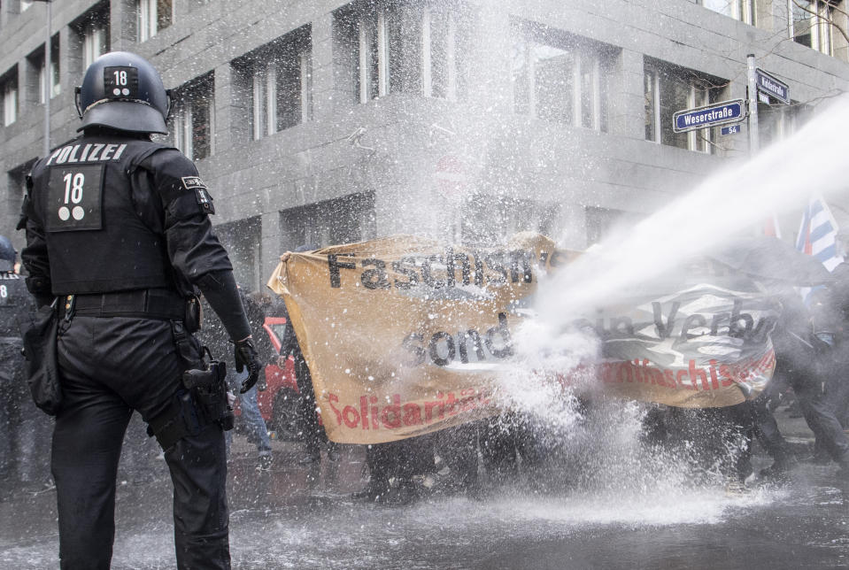 """The police use a water cannon on the opponents of the """"lateral thinking"""" demonstration in the city centre under the motto """"No lockdown for Bembeltown! """" in Frankfurt, Germany, Saturday, Nov.14, 2020. (Boris Roessler/dpa via AP)"""
