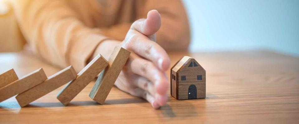 Woman hand stopping risk the wooden blocks from falling on house,