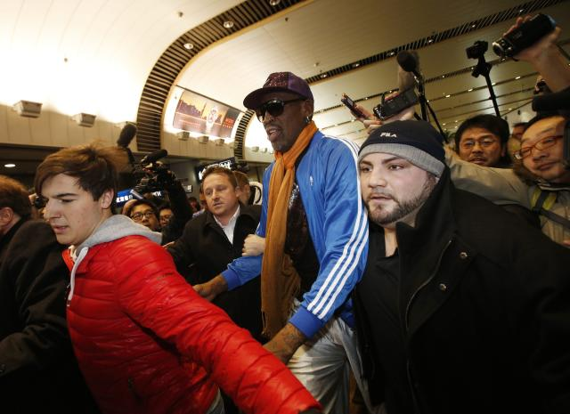 Bodyguards of Dennis Rodman make a way amidst the surrounding journalists upon his arrival from North Korea's Pyongyang at Beijing Capital International Airport