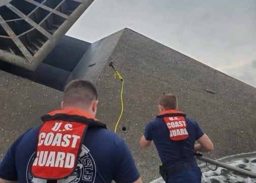 Coast Guard crew members attempt to throw a hammer at the hull of the SeaCor Power. The crew was attempting to make contact with potential survivors inside the vessel.
