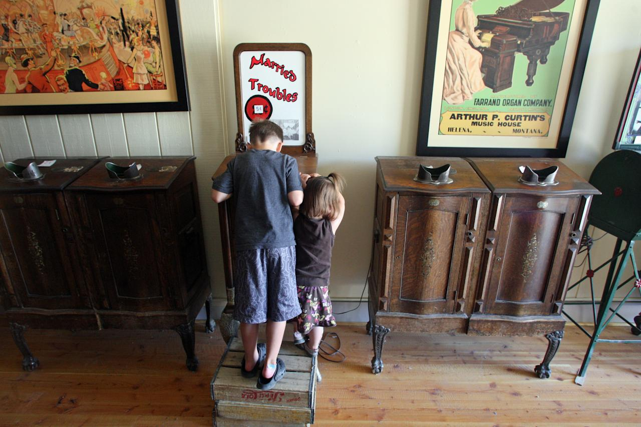 In this July 28, 2011 photo, young visitors try an antique picture machine at the Gypsy Museum in Virginia City, Mont. The Gypsy Museum houses an antique Gypsy fortune teller machine, that sat for decades in a Virginia City, Mont., restaurant and has received a multimillion dollar offers from curators including magician David Copperfield. Collectors say the 100-year-old machine that speaks your fortune may be the last of its kind. (AP Photo/Michael Albans)