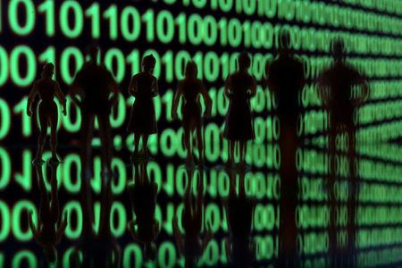 FILE PHOTO: Small toy figures are seen in front of a binary code in this illustration picture