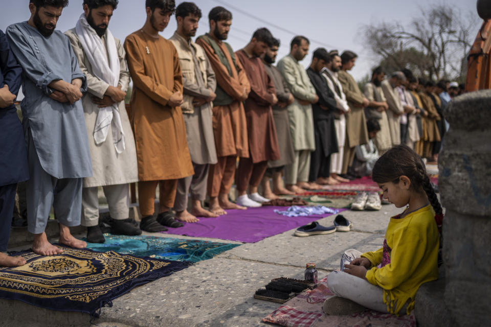 A girl working as a shoe cleaner sits in the street while men stand together during Friday prayers in Kabul, Afghanistan, Friday, Sept. 24, 2021. (AP Photo/Bernat Armangue)