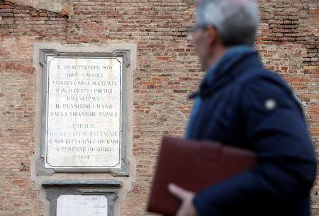 "A man walks in front of a 136 year-old plaque honouring the victims of "" Papal tyranny"" after Pope Francis celebrated a Mass in Carpi, Italy, April 2, 2017. REUTERS/Alessandro Garofalo"