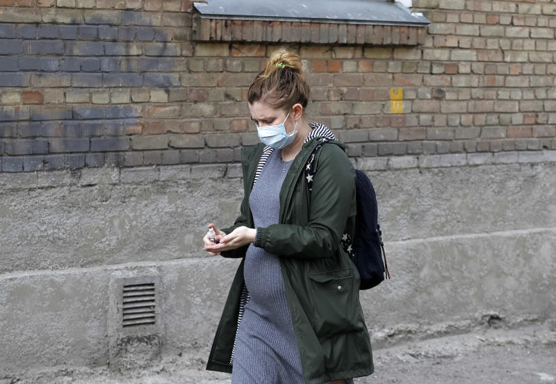 KIEV, UKRAINE - 2020/04/13: A pregnant woman wearing a face mask as a preventive measure against the spread of coronavirus disinfects her hands on the street. As on 13 April 2020 were 3102 laboratory confirmed of the COVID-19 coronavirus cases in Ukraine, 93 of which were lethal, 97 patients recovered. During the day, 325 new cases were recorded. (Photo by Pavlo Gonchar/SOPA Images/LightRocket via Getty Images)