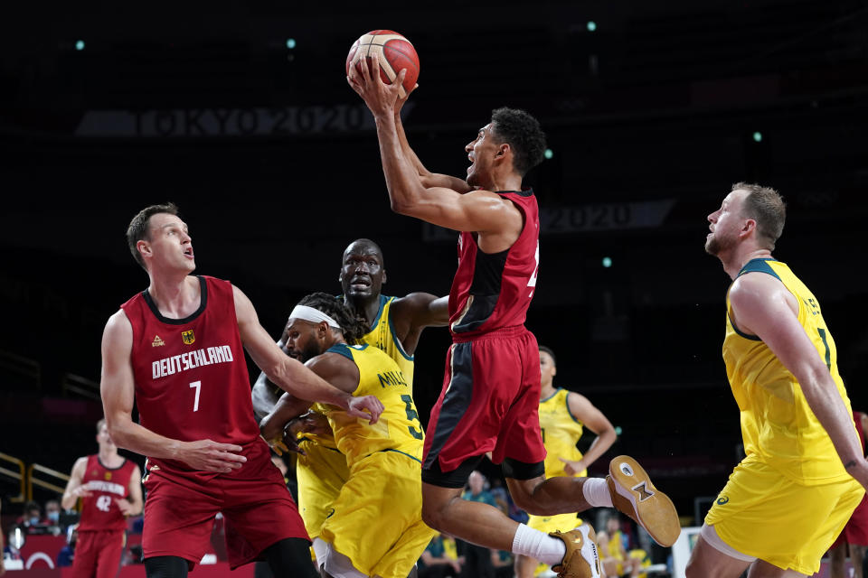 Germany's Maodo Lo, center, drives to the basket between teammate Johannes Voigtmann (7) and Australia's Joe Ingles (7) during a men's basketball preliminary round game at the 2020 Summer Olympics, Saturday, July 31, 2021, in Saitama, Japan. (AP Photo/Charlie Neibergall)