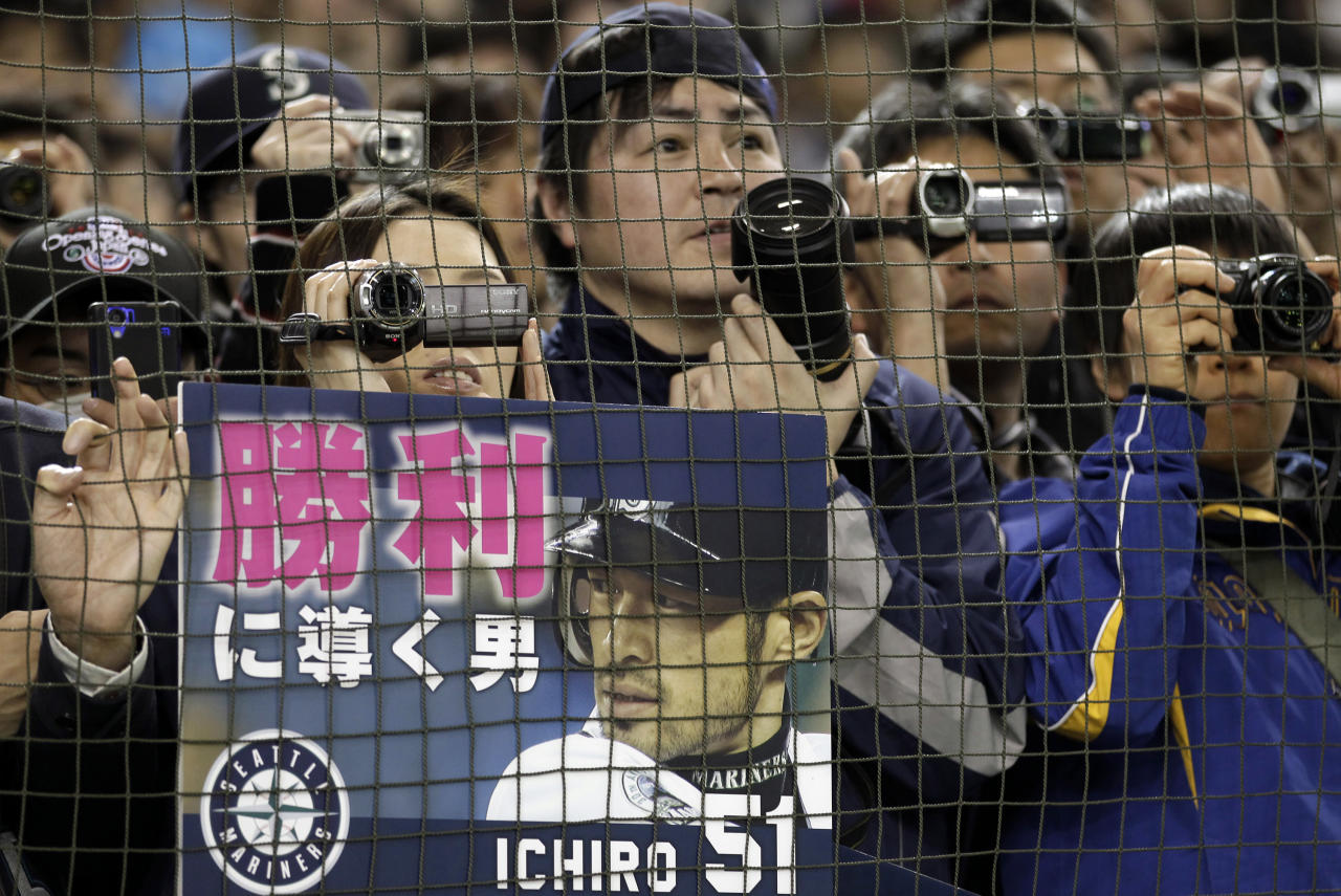 """Fans with a placard cheering Seattle Mariners outfielder Ichiro Suzuki watch the team's batting practice prior to the American League season opening MLB baseball game between the Oakland Athletics and the Mariners at Tokyo Dome in Tokyo, Wednesday, March 28, 2012. The placard reads: """"The man who leads to victory."""" (AP Photo/Shizuo Kambayashi)"""