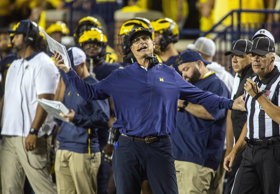 Michigan head coach Jim Harbaugh , center, reacts to a referee's penalty call against his team in the first quarter of an NCAA college football game against Washington in Ann Arbor, Mich., Saturday, Sept. 11, 2021. (AP Photo/Tony Ding)