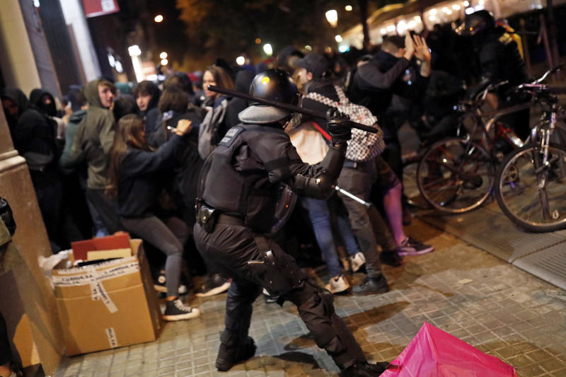 A policeman uses his baton again pro-independence demonstrators in Barcelona, Spain, Thursday, Oct. 17, 2019. Catalonia's separatist leader vowed Thursday to hold a new vote to secede from Spain in less than two years as the embattled northeastern region grapples with a wave of violence that has tarnished a movement proud of its peaceful activism. (AP Photo/Bernat Armangue)