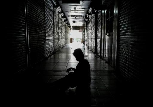 """A homeless person sleeps outside shops in the """"Roberto Huembes"""" market that are closed during a 24-hour nationwide general strike called by the opposition in Nicaragua"""